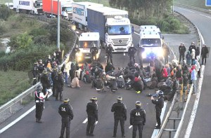 Copyright:Kerry Davies/Daily Mail 2/08/2015 Immigrants last night made another attempt to rush the Channel Tunnel but were beaten back by police with tear gas. They then staged a sit-in on the main lorry route to the tunnel blocking vehicles for the entire night until they were dispersed by riot police. picture shows: Immigrants staging the sit-in blocking lorries.